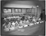 Children and priest in Holy Family School Cafeteria, Clarkston, Washington, March 22, 1949