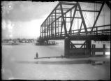 Kiona bridge, river frozen over. Marjorie standing on ice, Jan. 1909