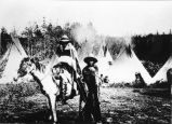 Two Yakama men in blankets, tepees in background, circa 1910s
