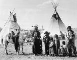 Family and horse by teepees