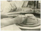 A pair of hands shape a piece of pottery on a potter's wheel