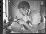 Louis Mideke working with a ceramic pot, circa 1955