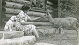 Trixie and Marguerite Bolton play with deer on the steps of Mountain Lake Cottage
