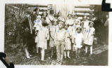 Group of children in front of log cabin