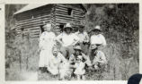 Group portrait in front of a log cabin