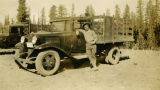 Man leaning against USFS truck, Mount Misery, Washington, 1933