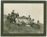 A girl with a gun sitting with her friends on a hill, Mica peak, Washington, circa 1900-1919