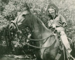 A smiling Pat Woodell on horseback