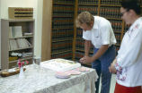Jan Kielpinski, city attorney, cutting cake