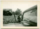Unidentified young woman leaning through the window of a parked vehicle