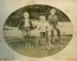 Three young boys and a tricycle
