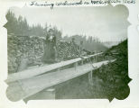 A woman and two men standing beside a cordwood flume on Moore Creek