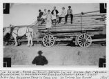 Local residents on top of lumber wagon pulled by horses Lumber wagon